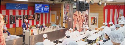 市場内に大きな枝肉をつるして行うセリの様子=京都食肉市場株式会社提供